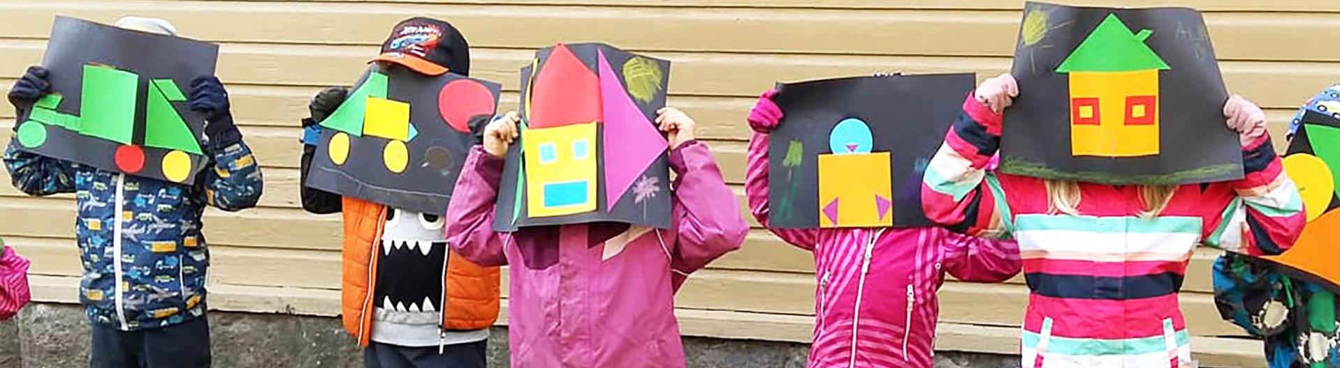 Lapsia ulkoiluvaatteissa kellertävän lautaseinän edessä. Kaikki pitelevät kollaasiteoksiaan kasvojensa edessä.